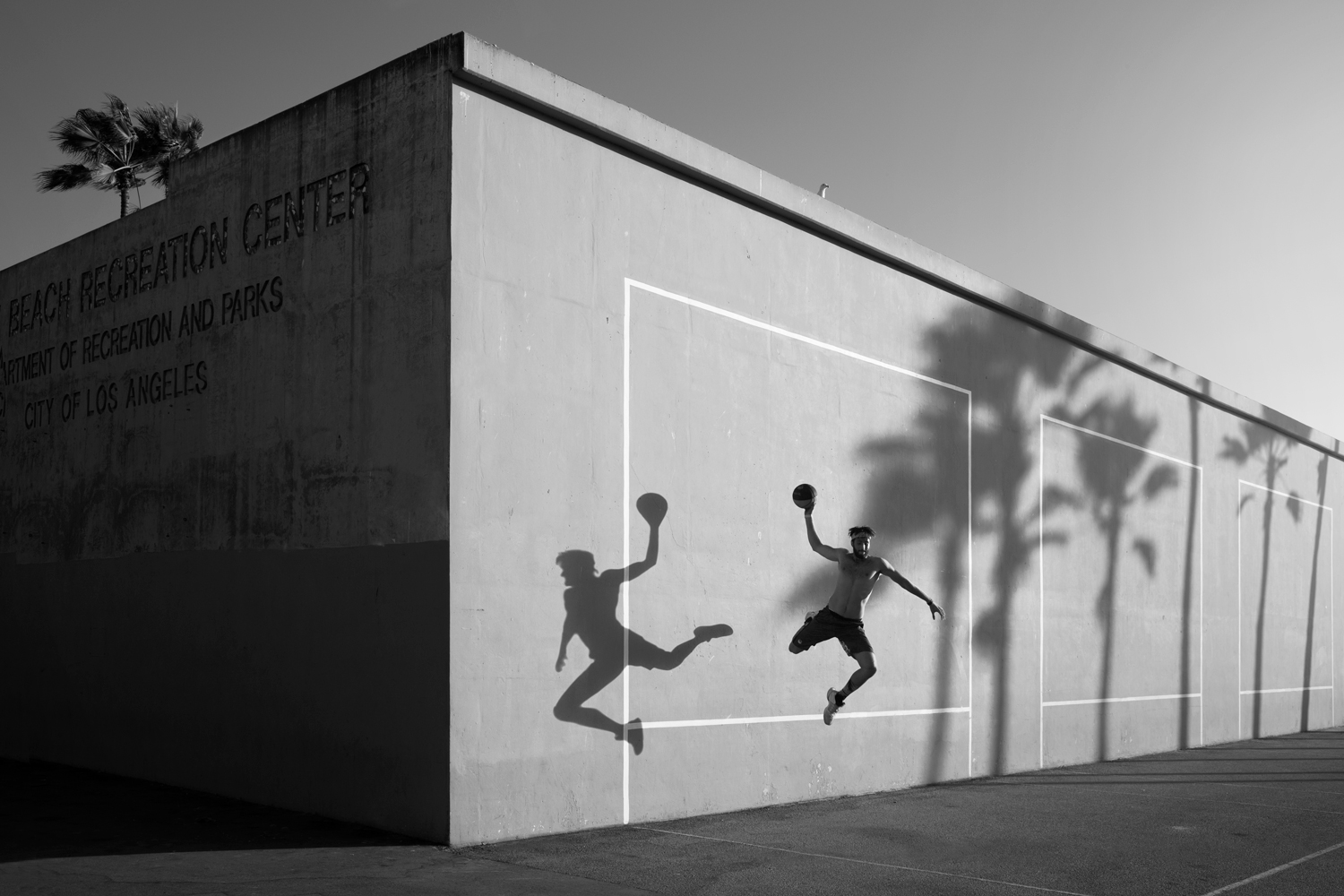 Guy jumping in front of the venice beach tennis court with his shaddow on the wall