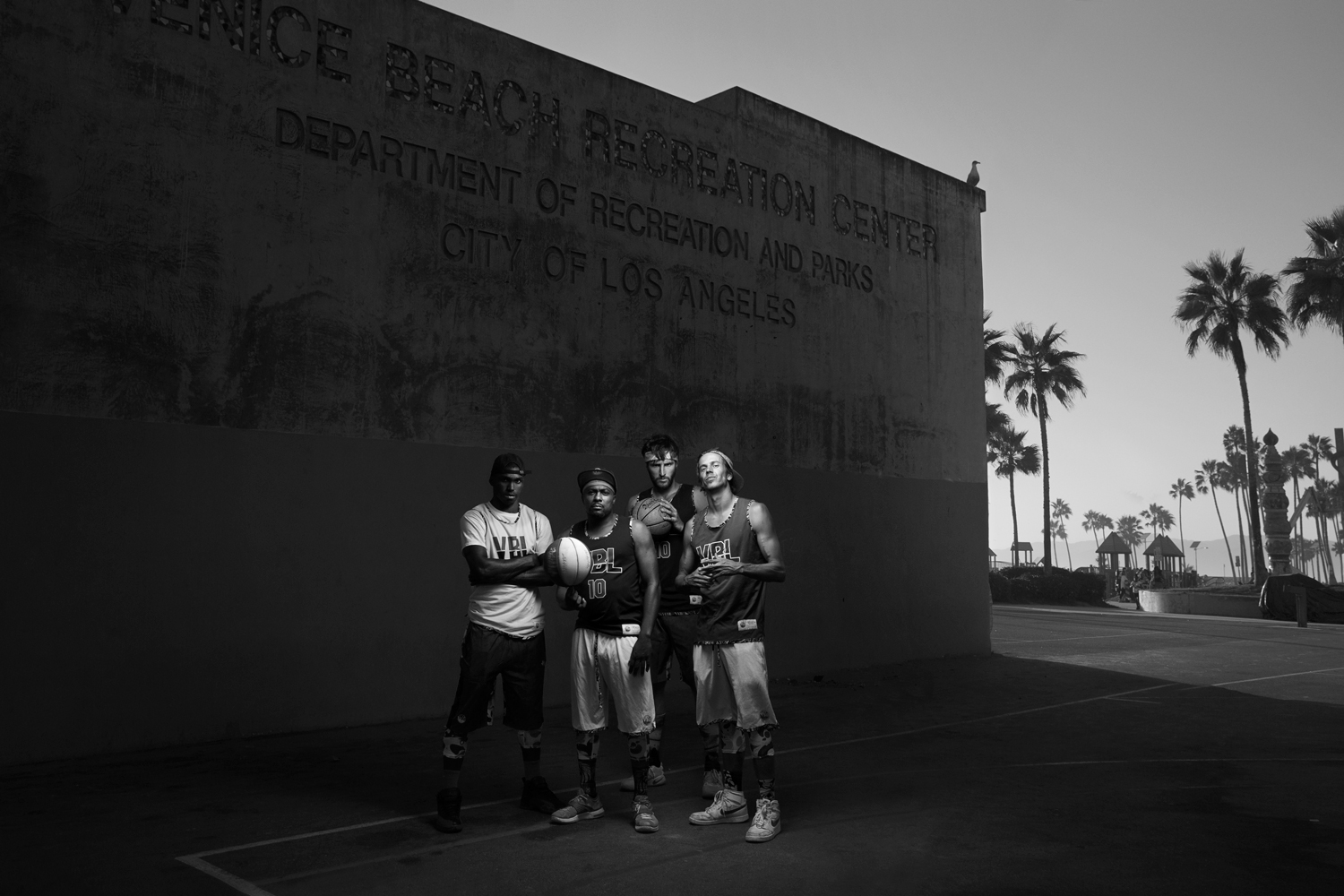 A group picture of young basketball players on a venice beach basketball court with palm trees in the background