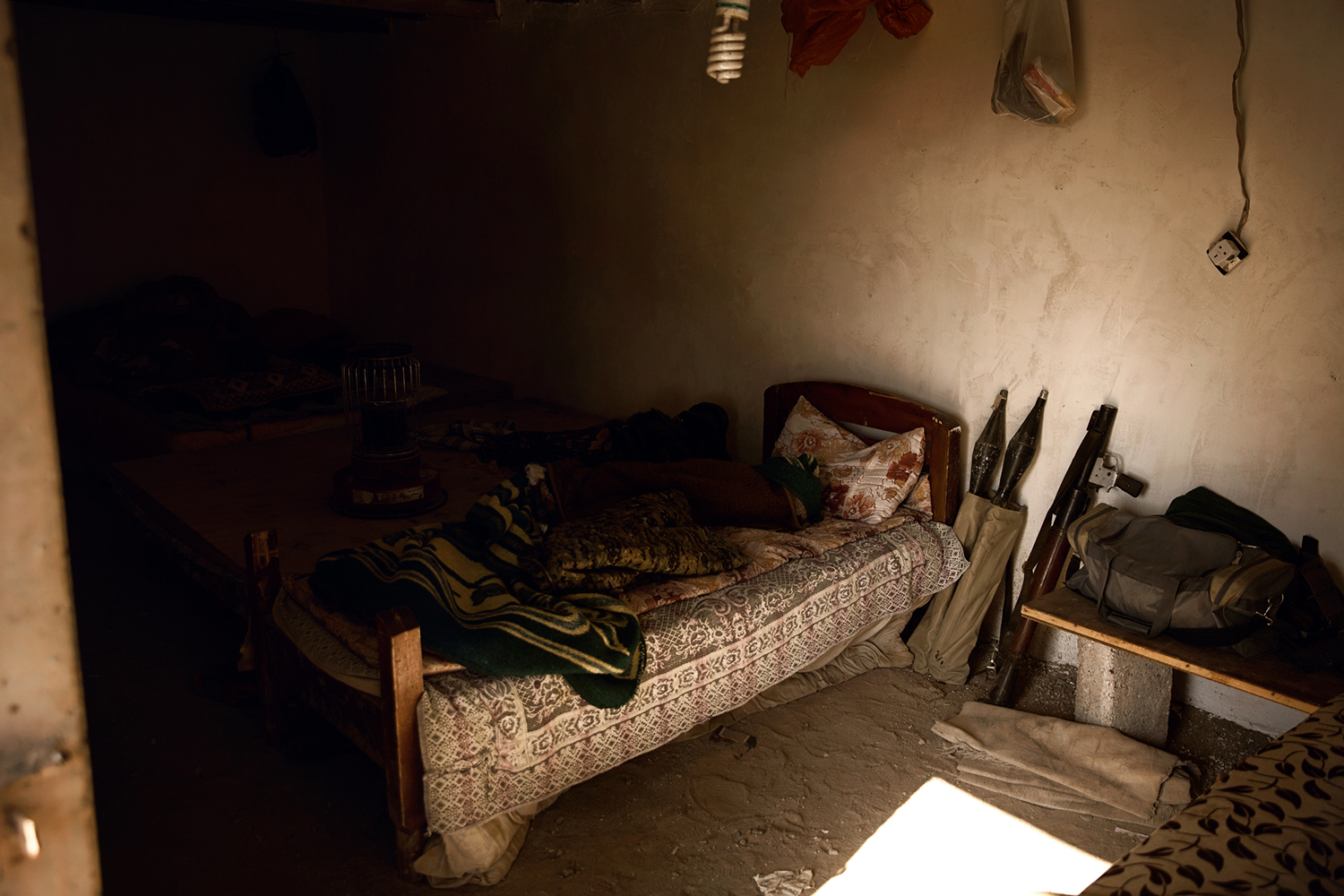 A Peshmerga soldiers bedroom with weapons next to it on the frontline