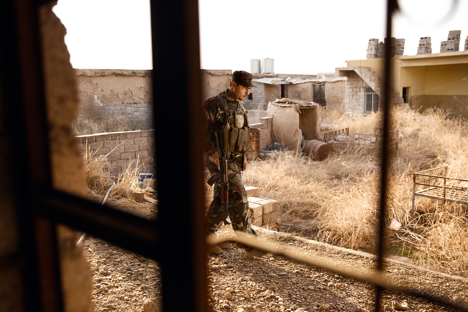 A Peshmerga fighter with his weapon in the ruins of a kurdish town
