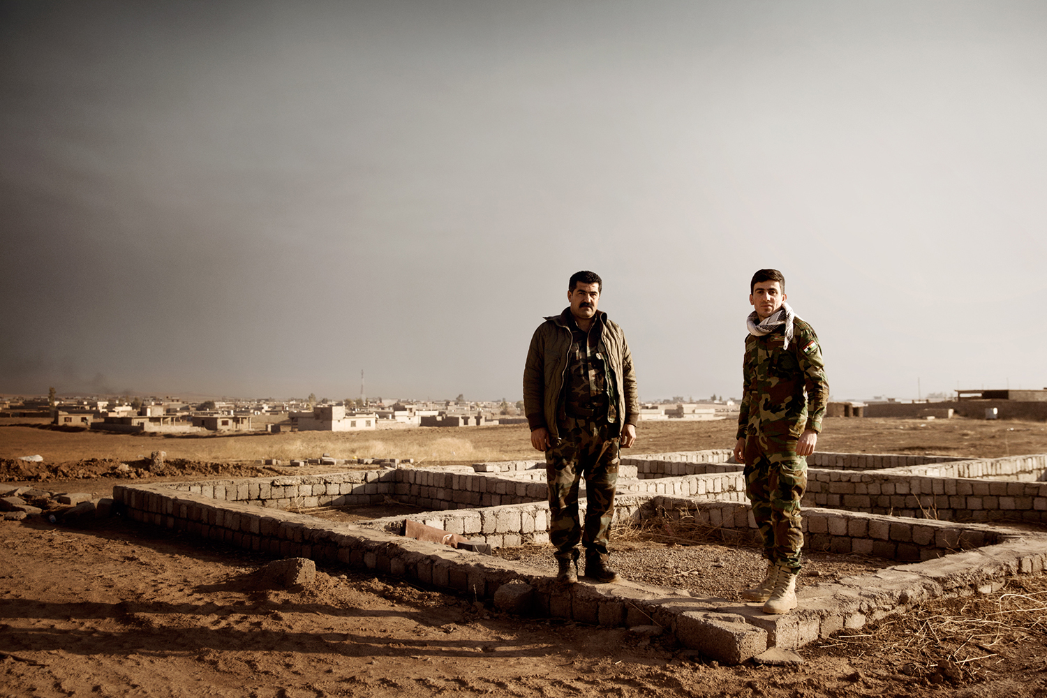 Two Peshmerga soldiers in front of a destroyed town in Kurdistan