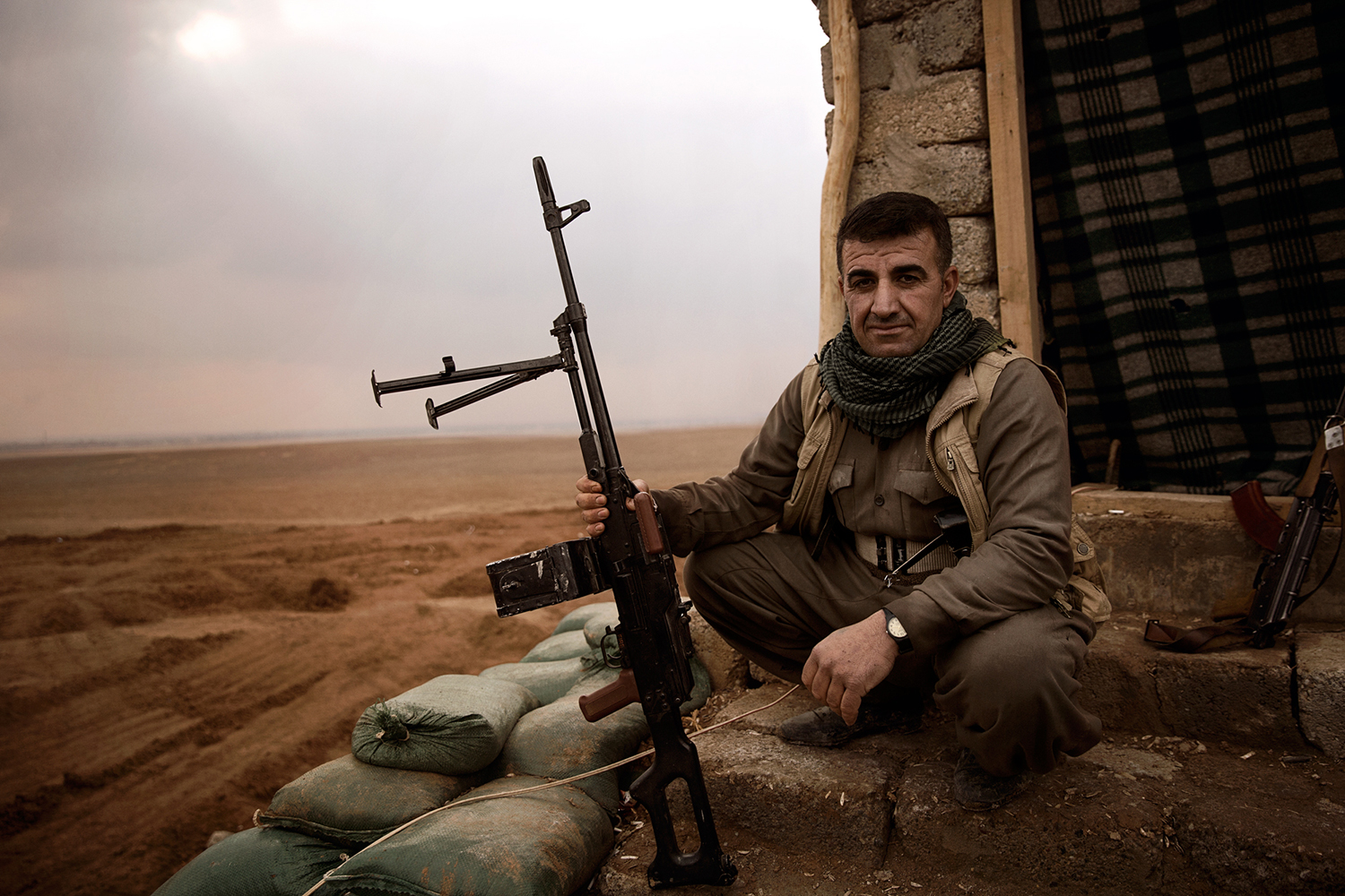 A kurdish Peshmerga fighter with his weapon in front of the Iraqi border